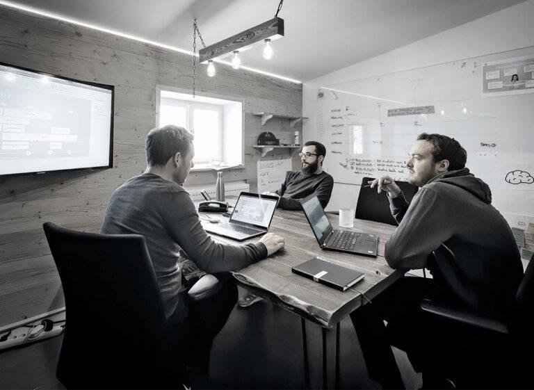 3 Personen mit Laptops im Meeting